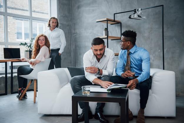 Interacción completa grupo de trabajadores de oficina multirraciales en ropa formal hablando sobre tareas y planes