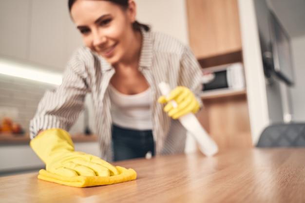 Interacción en el hogar. alegre mujer morena manteniendo una sonrisa en su rostro mientras limpia su cocina