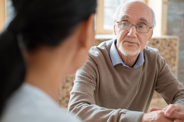 Interacción social. hombre senior positivo guapo con gafas mientras escucha a un voluntario y posando sobre fondo borroso