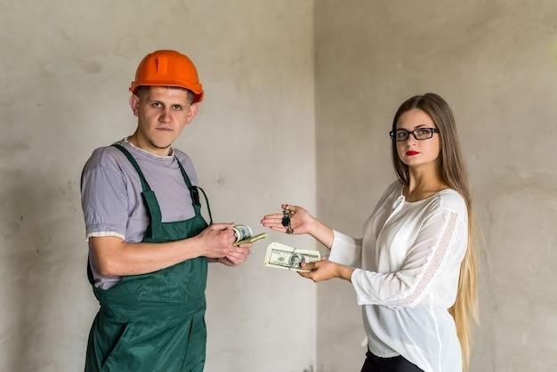 Intercambio entre constructor de hombre con llaves y mujer con dinero