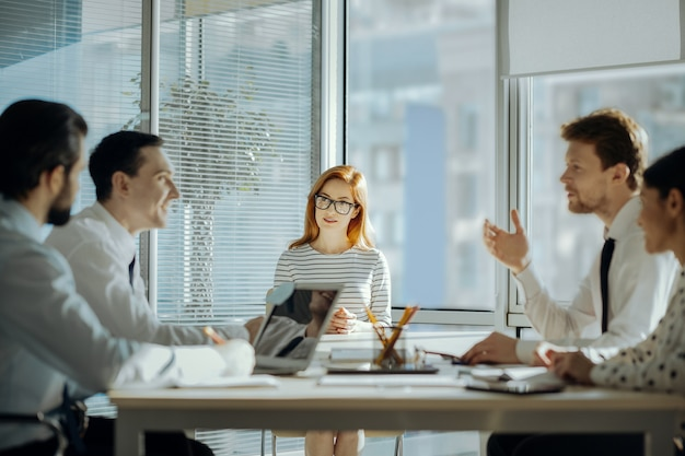 Intercambio de ideas. compañeros jóvenes optimistas sentados en la mesa uno frente al otro y discutiendo las tareas del trabajo durante la reunión con su jefe sentado en la cabecera de la mesa