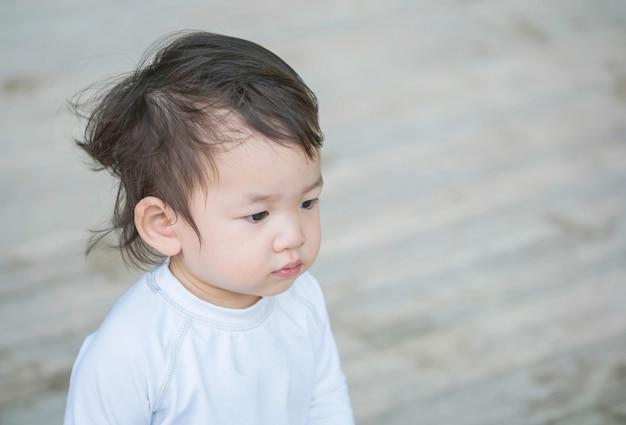 Interés asiático lindo del niño del primer en algo emoción