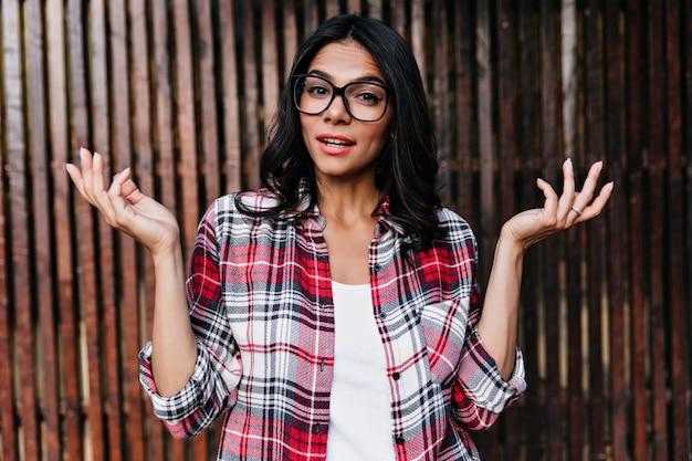 Interesada chica de pelo negro agitando las manos en la pared de madera. curiosa dama hermosa posando en elegantes gafas.
