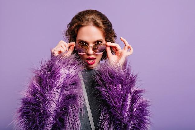 Interesada mujer adorable con maquillaje brillante mirando a través de gafas de sol oscuras