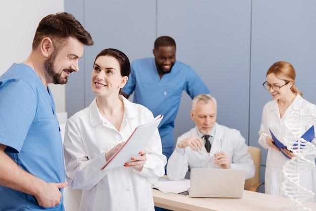 Interesado en tu opinión. doctores talentosos involucrados positivos que estudian y disfrutan de la conferencia en la clínica mientras mejoran las calificaciones e intercambian opiniones