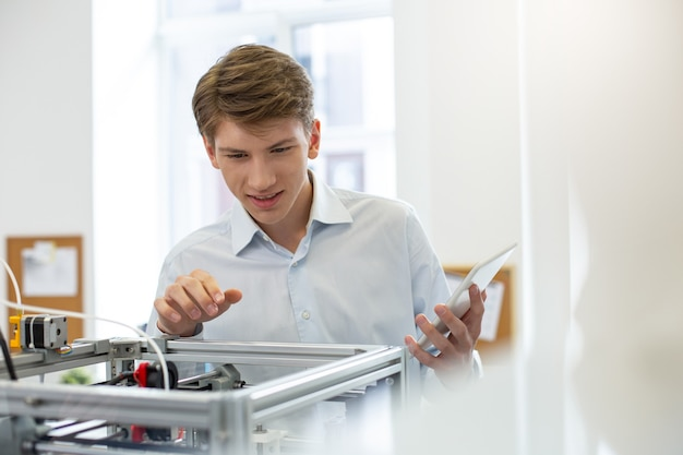Interesante descubrimiento. trabajador de oficina joven encantador sonriendo agradablemente mientras mira dentro de la impresora 3d y descubre algo nuevo sobre su mecanismo