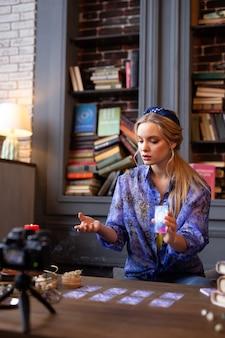 Interesante profesión. bonita mujer rubia sosteniendo una carta del tarot siendo un adivino