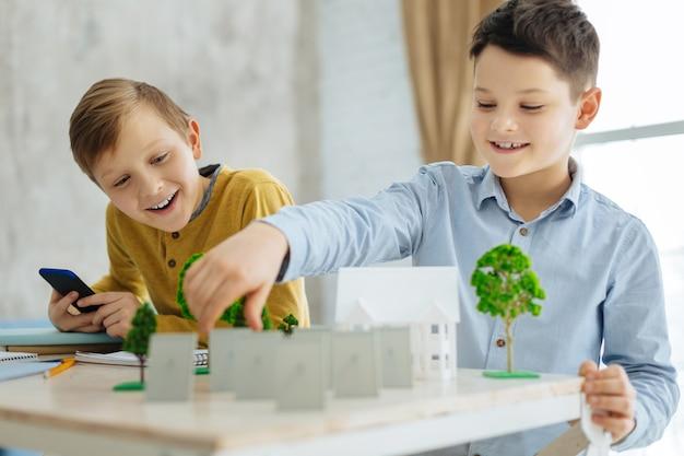 Interesante proyecto. dos niños preadolescentes agradables y alegres que crean los modelos de barrio en miniatura, colocándolos con cuidado sobre la mesa, mientras trabajan en el proyecto de ecología