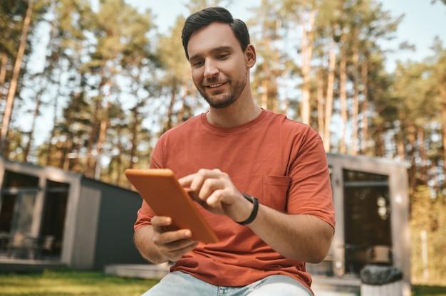 Interesar. hombre sonriente de pelo oscuro mirando con interés la pantalla táctil de la tableta sentado descansando al aire libre en un día soleado
