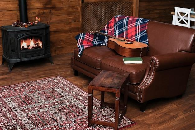 Interior acogedor con guitarra en el sofá