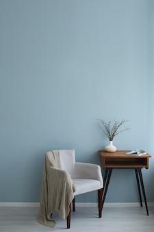 Interior acogedor de sillón retro mesa de madera vintage con revista y florero en el fondo de la pared azul y piso de madera.