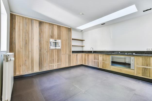 Interior de amplia cocina con muebles de madera y electrodomésticos modernos en apartamento nuevo