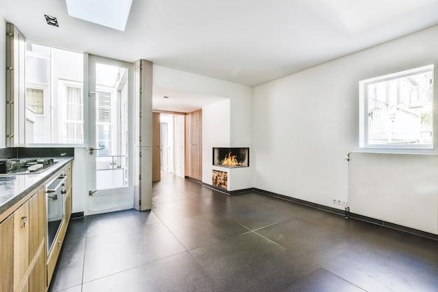 Interior de amplia cocina con muebles modernos y chimenea en casa iluminada con luz solar