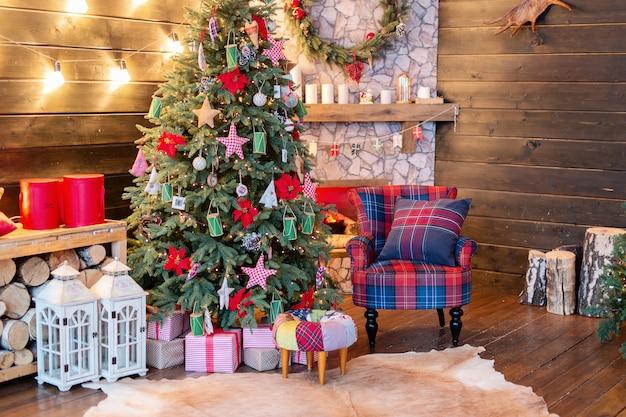 Interior de año nuevo, vacaciones, navidad, acogedor y cálido. árbol de navidad y chimenea