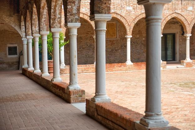 Interior de la antigua casa de ladrillo con columnas en venecia, italia