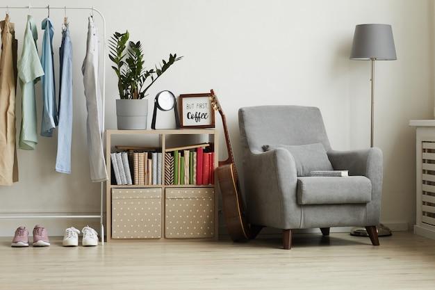 Interior del apartamento con un diseño minimalista, centrado en un cómodo sillón gris y perchero contra la pared blanca