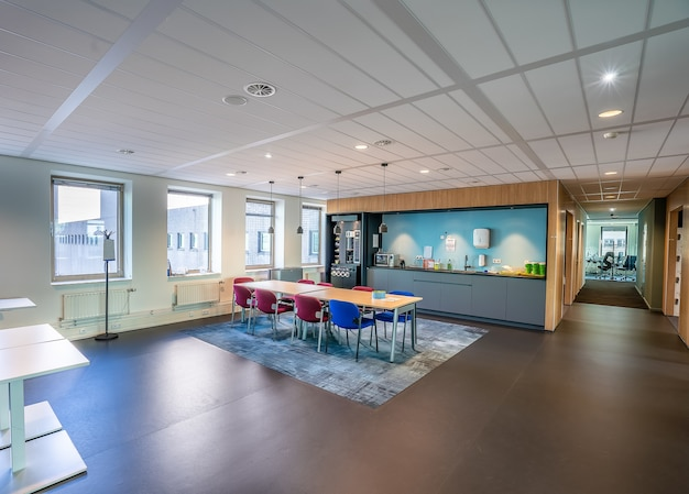 Interior del área de la cocina de una oficina moderna con una larga mesa y sillas de madera