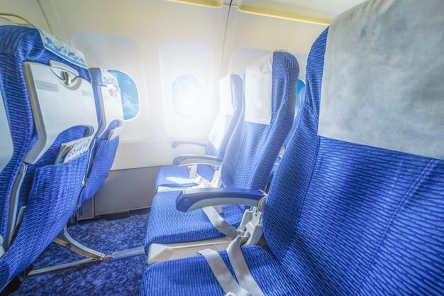 Interior de asientos vacíos de un avión en el día.