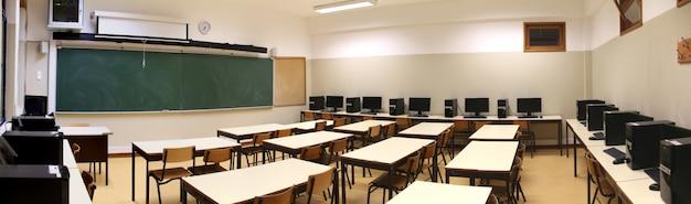Interior de un aula con fila de computadoras