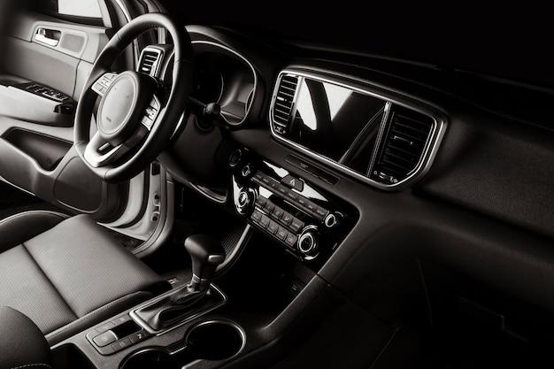Interior del auto nuevo con detalles lujosos, asientos de cuero y pantalla táctil.