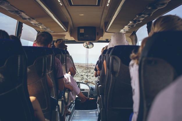 El interior del autobús turístico con gente sentada. vista trasera.