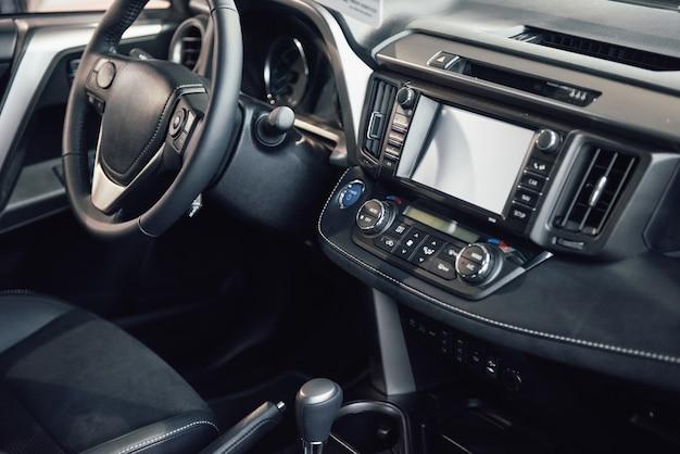 Interior del automóvil de lujo: volante, palanca de cambios, tablero y computadora