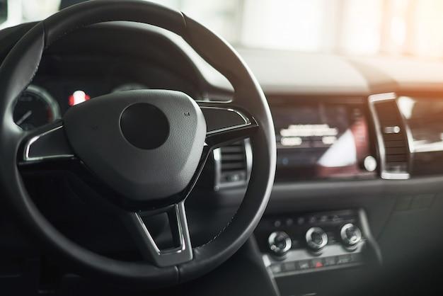 Interior del automóvil de lujo: volante, palanca de cambios y tablero de instrumentos