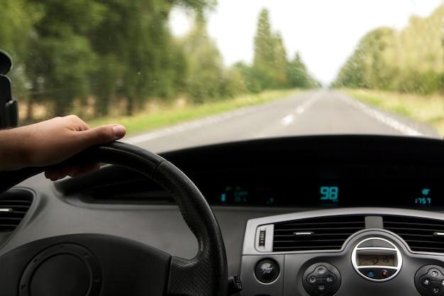 Interior del automóvil con la mano del conductor en la carretera en una pista en clima lluvioso