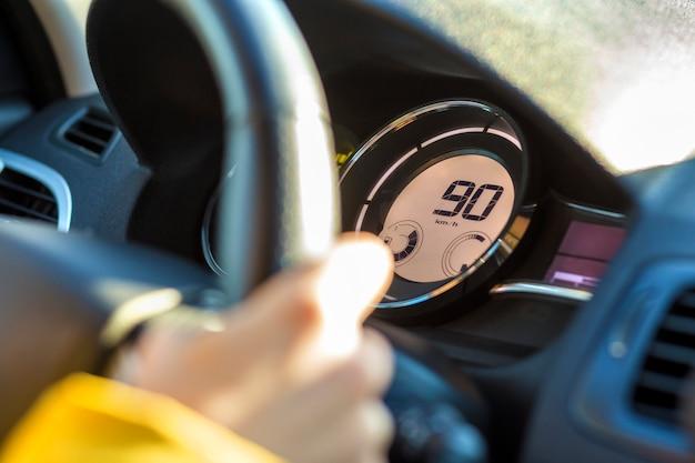 Interior del automóvil moderno con la mano del conductor en el volante y noventa km en el velocímetro. concepto de conducción segura
