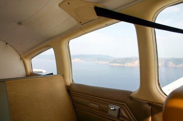 Interior de avioneta en vuelo con vista desde la ventana de la costa de mallorca