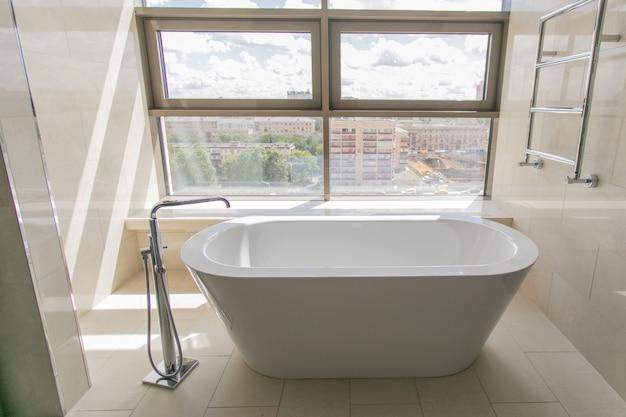Interior de baño blanco puro con bañera separada.