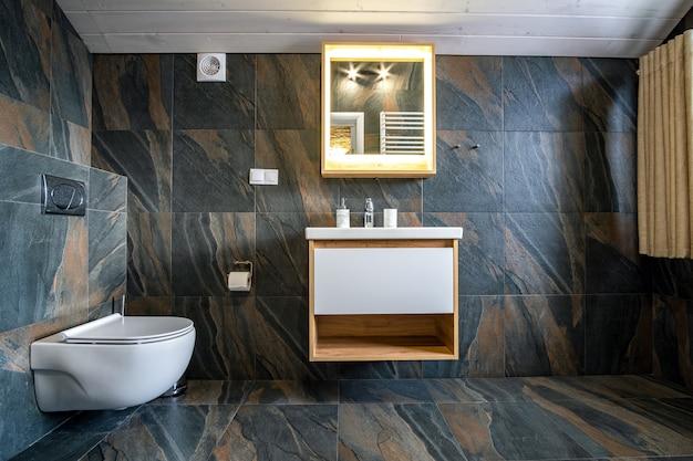 Interior de baño moderno y elegante con paredes de azulejos negros, cortina de ducha y muebles de madera con lavabo y espejo grande iluminado.