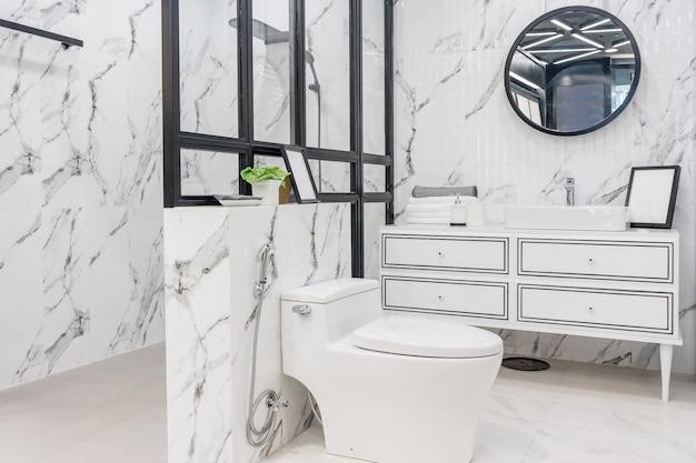 Interior del baño con paredes blancas, muebles vintage, toallas, inodoro y lavabo.