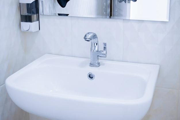 Interior del baño público limpio, lavabo blanco interior del baño público con lavado de manos y espejo