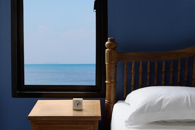 Interior blanco almohadas y sábanas en dormitorio azul con vistas al mar en verano por la mañana