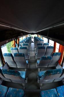 Interior del bus turístico para excursiones y viajes largos. un montón de asientos libres y lugares para maletas pequeñas.