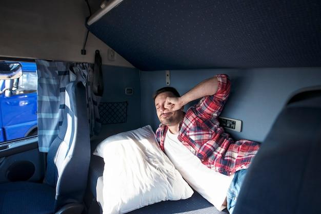 Interior de la cabina del camión con conductor durmiendo en la cama