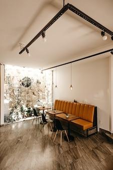 Interior del café con un sofá naranja, tres mesas y tres sillas negras.