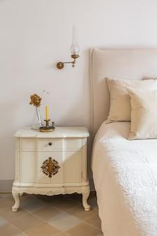 Interior de casa acogedora en dormitorio clásico de estilo retro con velas y flores en la mesita de noche de madera ...