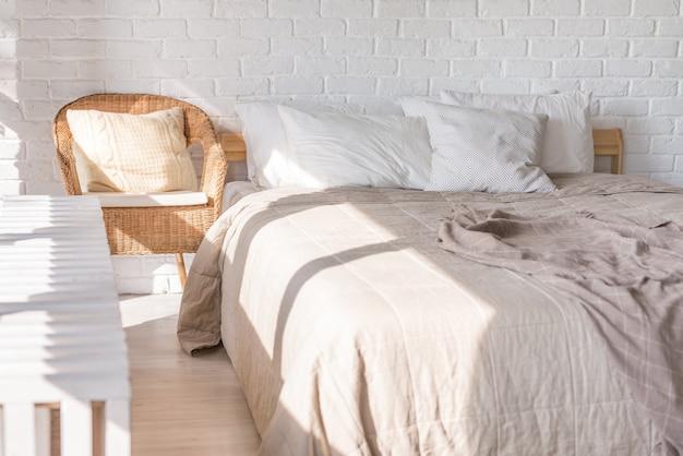 Interior de la casa, dormitorio en colores claros suaves con cama doble, colcha. almohadas