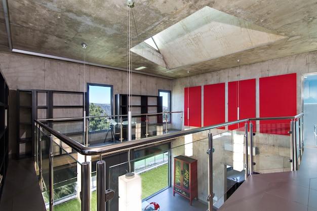 Interior de la casa moderna de hormigón, vista desde el segundo piso, lámparas rojas y paneles en la pared.