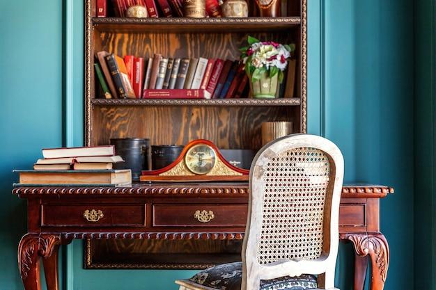 Interior clásico de lujo de la biblioteca del hogar. salón con estantería, libros, mesa y silla.