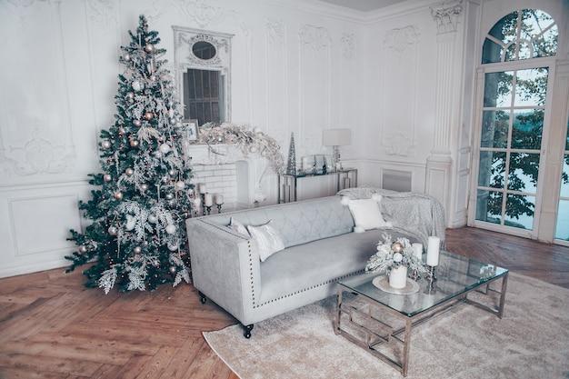 Interior clásico de navidad blanca con elementos modernos y árbol de año nuevo decorado.
