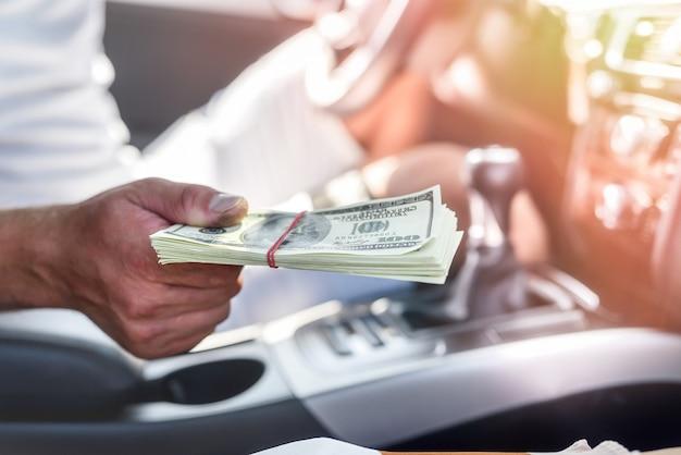 Interior del coche con mano masculina sosteniendo un paquete de dólares de cerca. imagen tonificada