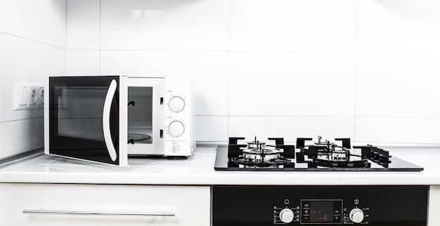 Interior de cocina moderna con cocina eléctrica y horno microondas.