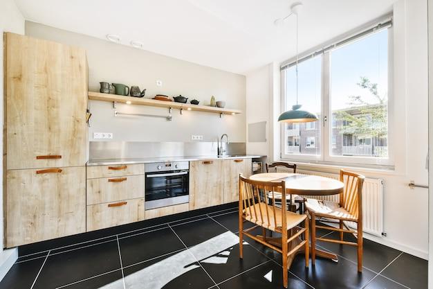 Interior de cocina moderna y luminosa. mesa redonda de madera con sillas ubicadas debajo de la lámpara cerca del estante con vajilla en el comedor luminoso durante el día