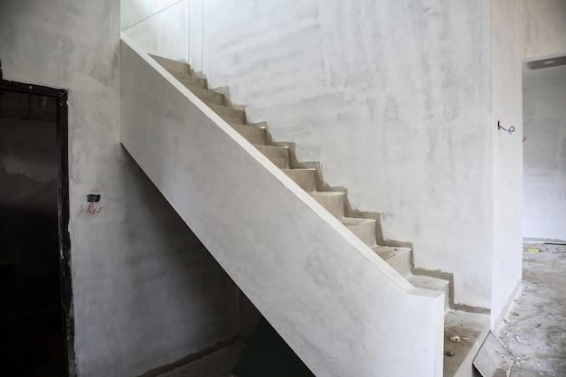 Interior de construcción de casa nueva con escalera de hormigón en obra