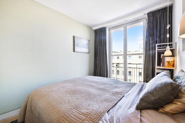 Interior de dormitorio amplio y luminoso con balcón en apartamento contemporáneo durante el día soleado