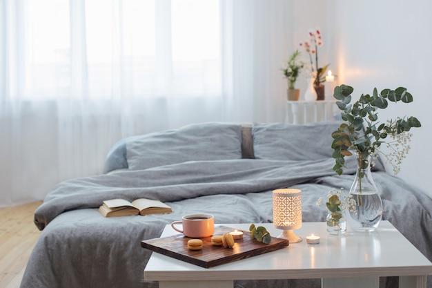 Interior de dormitorio con bouquet, velas y una taza de té.