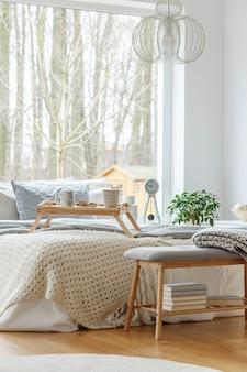 Interior del dormitorio con una cama king-size con almohadas y mantas grises, ventana grande y piso de madera